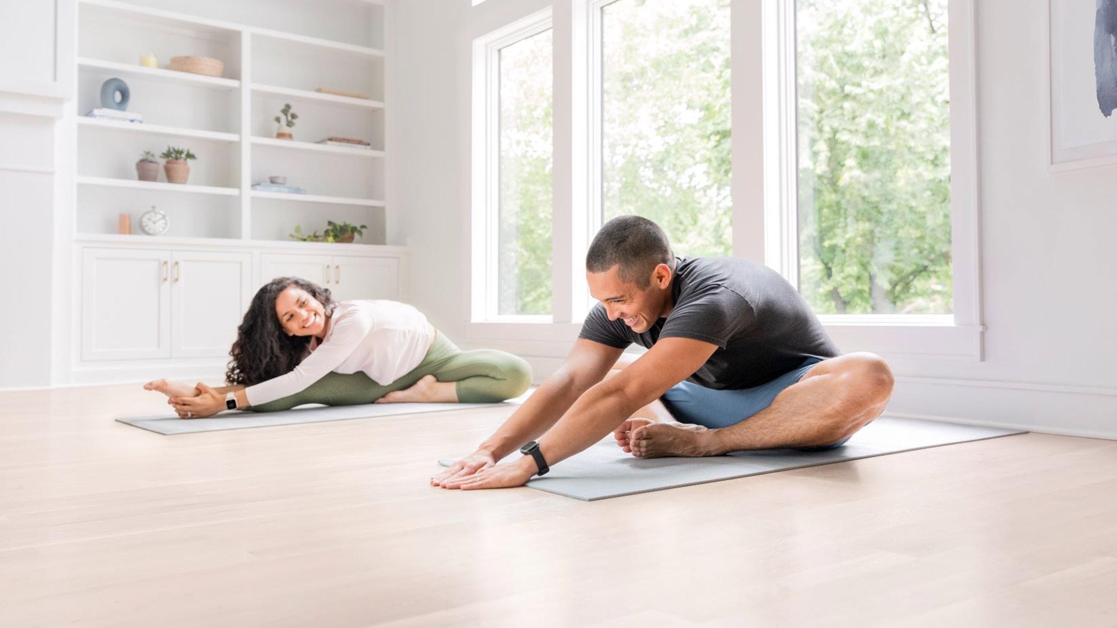 Ein Mann und eine Frau mit Venu Sq Music Smartwatch machen Dehnübungen auf Yogamatten.