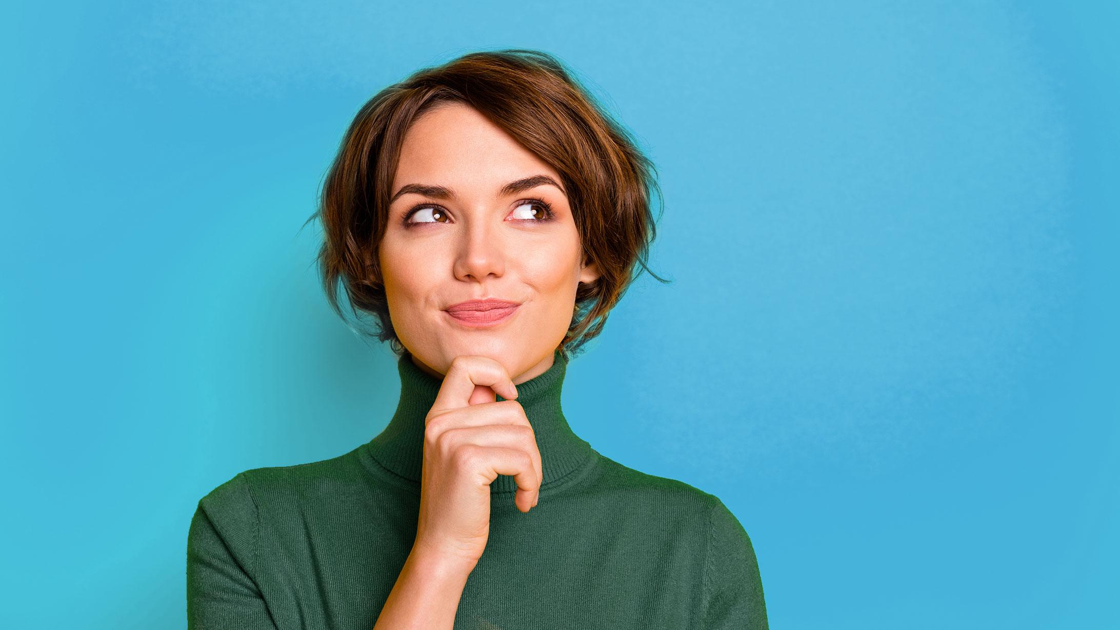 Eine Frau auf blauem Hintergrund schaut fragend nach Oben.