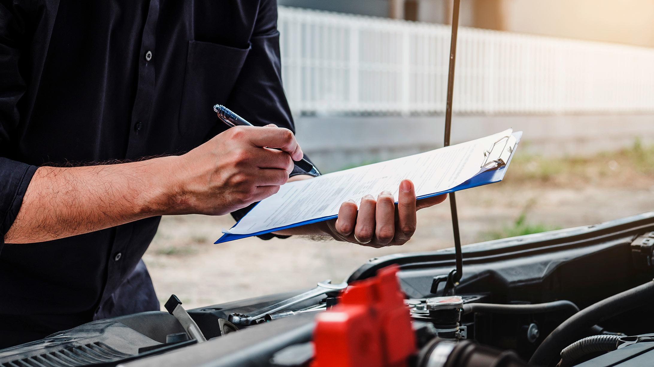 Person, die mit einer Checkliste ein Auto untersucht.