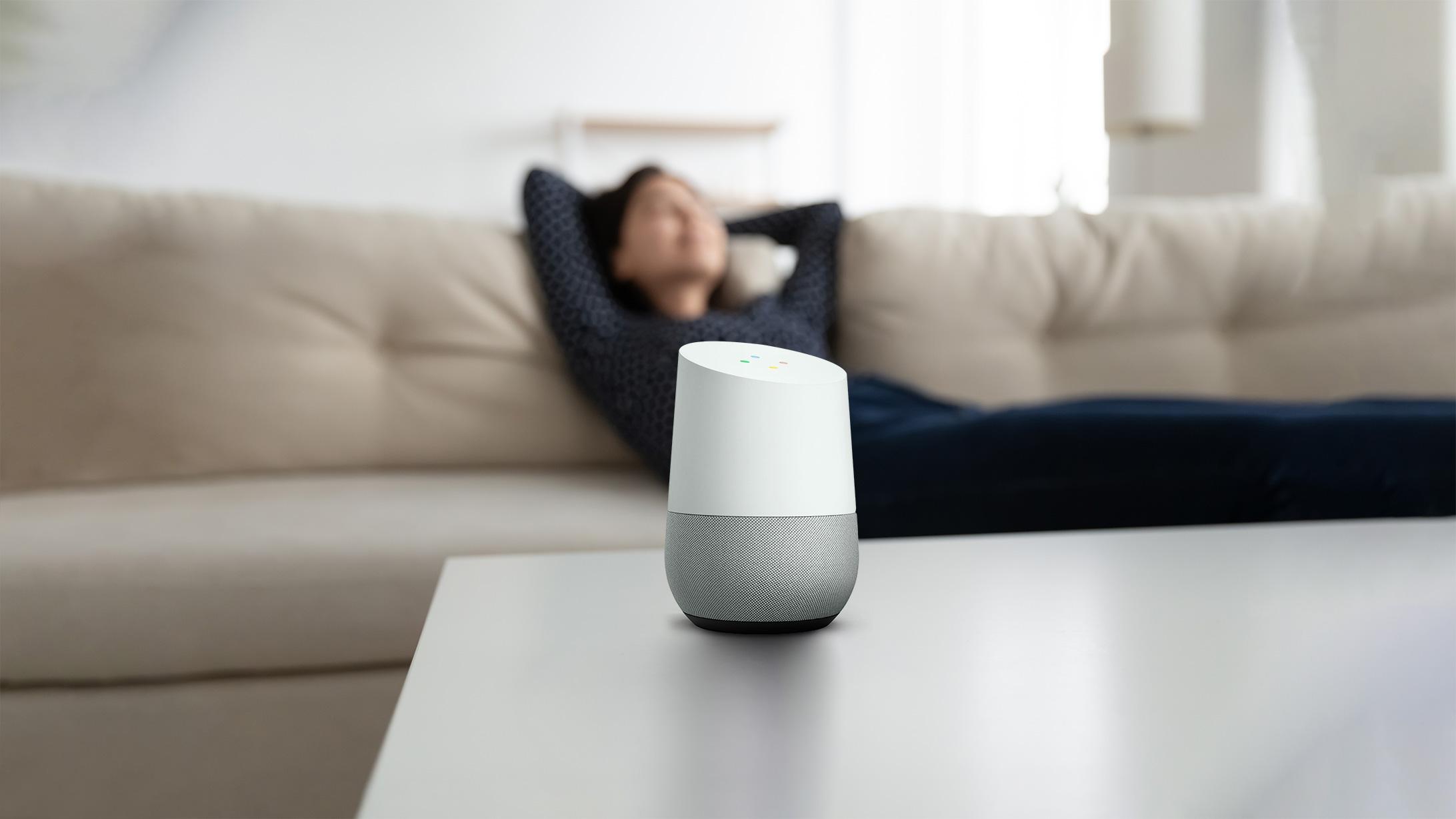 Google Home Smartspeaker auf einem Tisch mit Frau im Hintergrund auf dem Sofa.