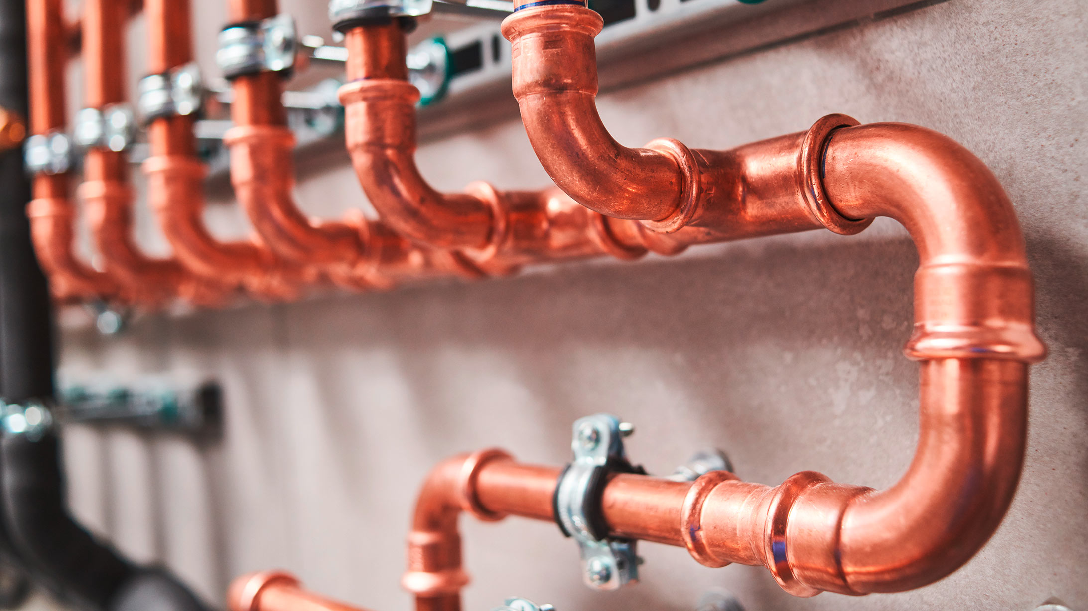 Orange-rote Heizungsrohre an einer Wand