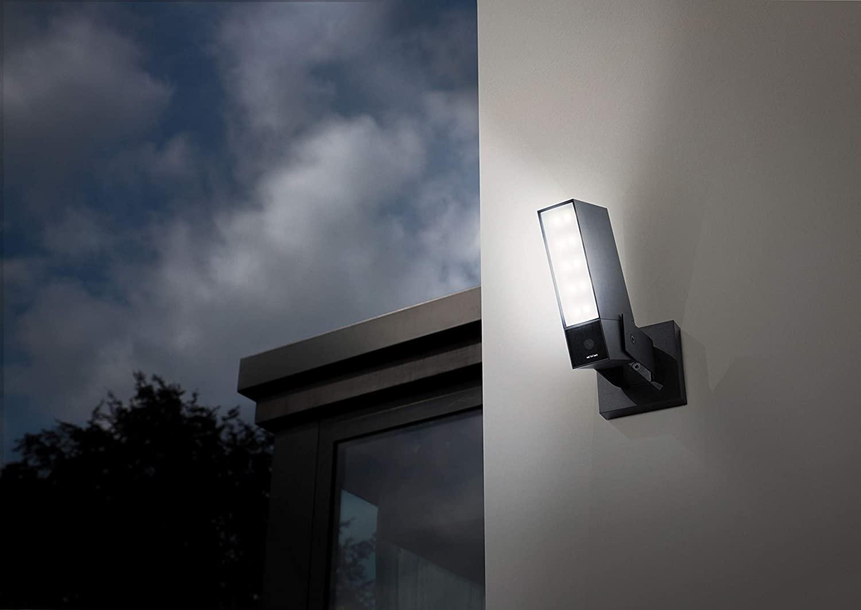 Überwachungskamera mit Flutlicht bei Nacht an Hausmauer